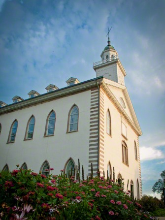 A side view of the front part of the Kirtland Temple, with a green and pink flowering bush in the foreground and light clouds in the distance.