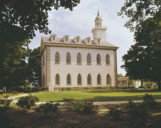 A side view of the Kirtland Temple, framed by large green trees on the sides.