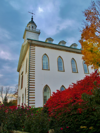 A view of the Kirtland Temple from below, looking upward on a fall day with a red bush in the foreground.