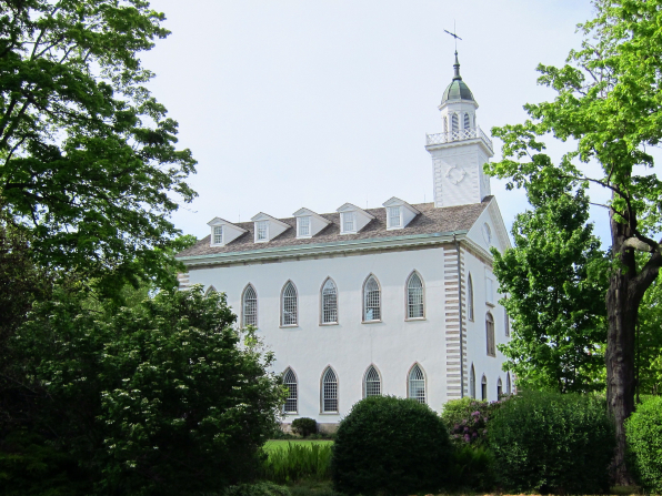 A side view of the Kirtland Temple, surrounded by large green trees and bushes.