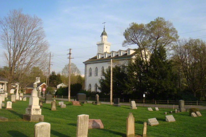 A cemetery near the Kirtland Temple, which is seen across the street on a sunny day.