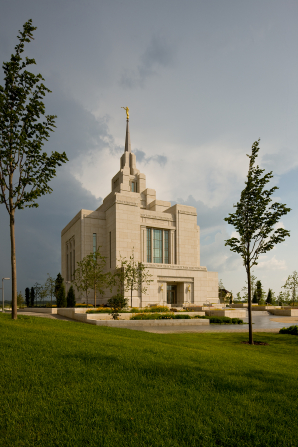 The Kyiv Ukraine Temple, taken from afar, with the green lawns and small trees growing in the foreground.