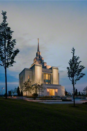 A portrait of the Kyiv Ukraine Temple illuminated at night, with several trees on the temple grounds in view.