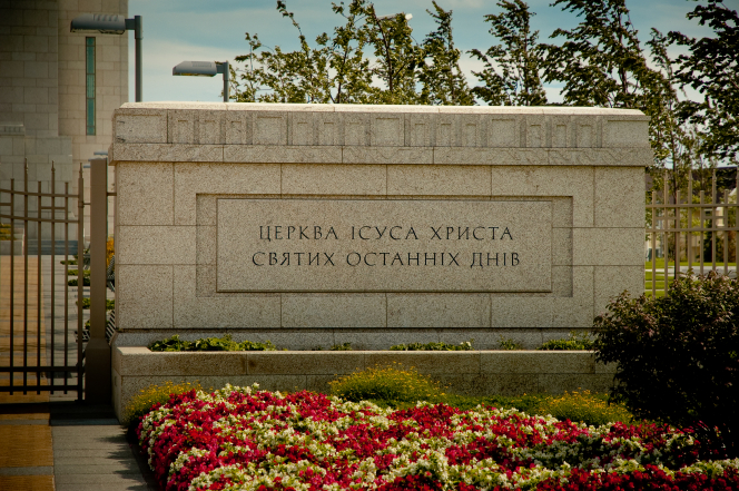 The granite sign outside of the gate to the Kyiv Ukraine Temple, with colorful flowers in front of it.