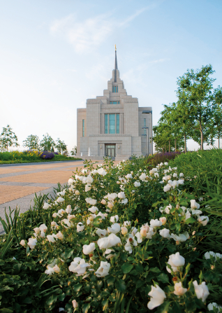 The flower-lined path leading to the Kyiv Ukraine Temple, on a sunny day with a pale blue sky in the distance.