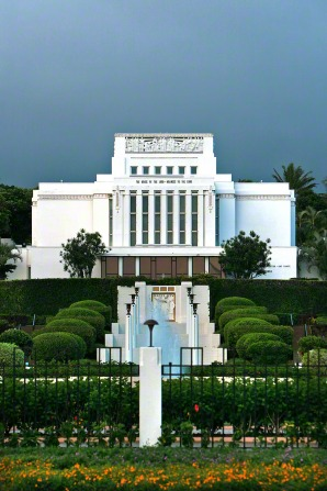 The front of the Laie Hawaii Temple, seen from a distance, with manicured green bushes leading up to the temple.
