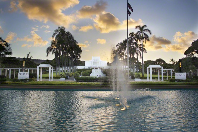 A large water feature on the grounds of the Laie Hawaii Temple, with the temple seen in the background in the evening.