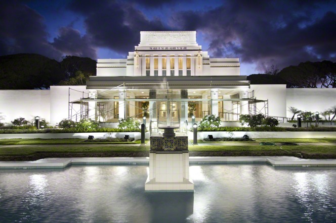 The fountain in front of the entrance to the Laie Hawaii Temple, at night, with the temple lit from inside and outside.