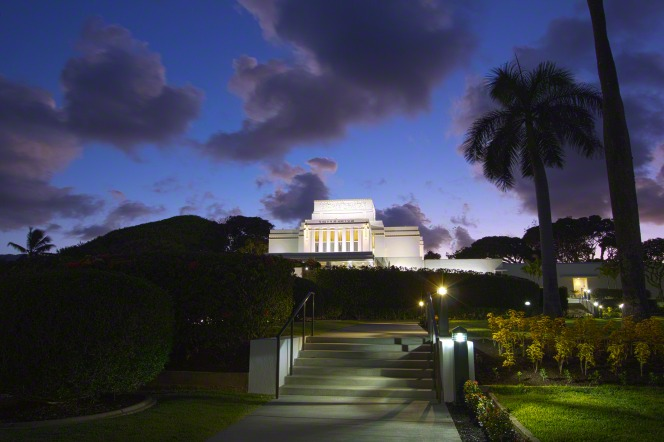 A set of stairs leading up to the Laie Hawaii Temple, which is seen in the distance atop a hill in front of a purple night sky.
