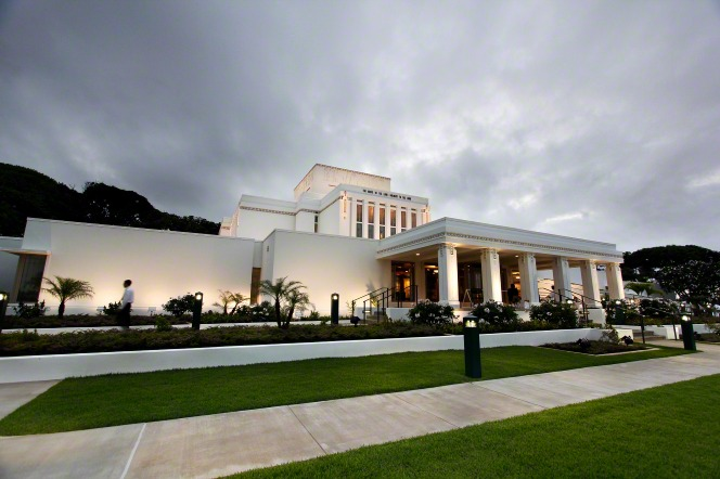 A wide-angle view of the front of the Laie Hawaii Temple in the evening, with the exterior lights turned on.