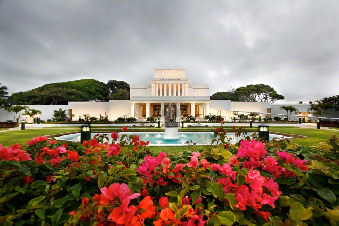 A wide-angle view of the Laie Hawaii Temple, with large pink flowers in the foreground and the temple in the background.
