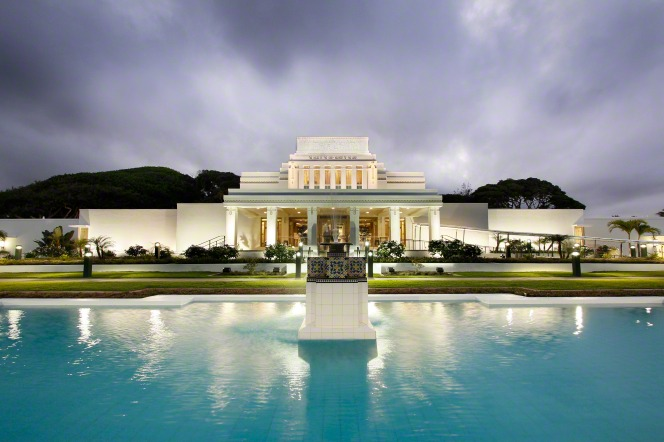 The front of the Laie Hawaii Temple at night, with the pool of water and fountain lit up near the entrance.