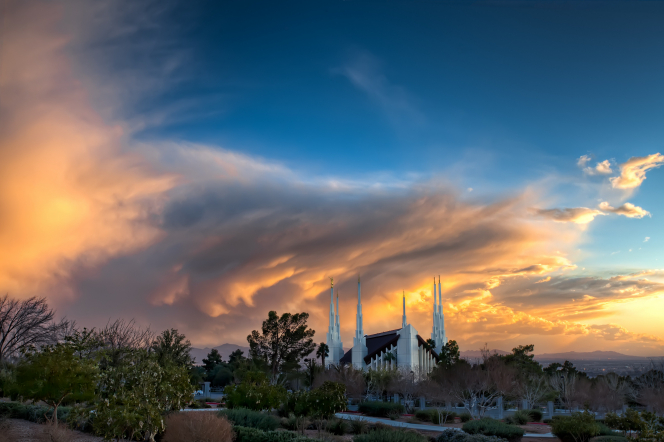 A distant view of the Las Vegas Nevada Temple at sunset, with orange light reflecting on the clouds overhead.