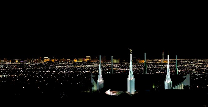 A far-off view of the Las Vegas Nevada Temple spires, illuminated with white light at night, with the city lights in the distance.