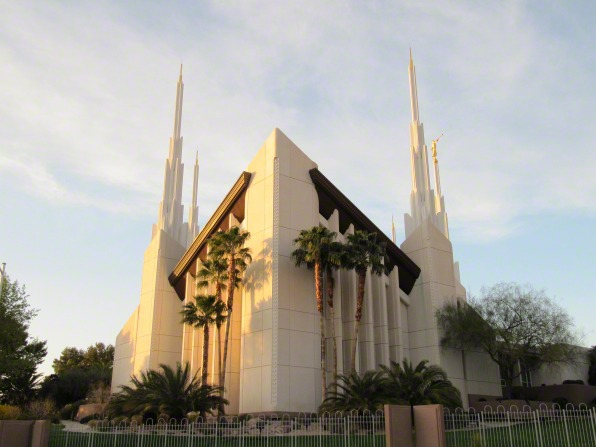 The front of the Las Vegas Nevada Temple, with palms and other trees and several of the temple's spires in view.