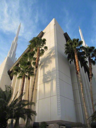 The front of the Las Vegas Nevada Temple from below, with palm trees growing near the walls of the temple.