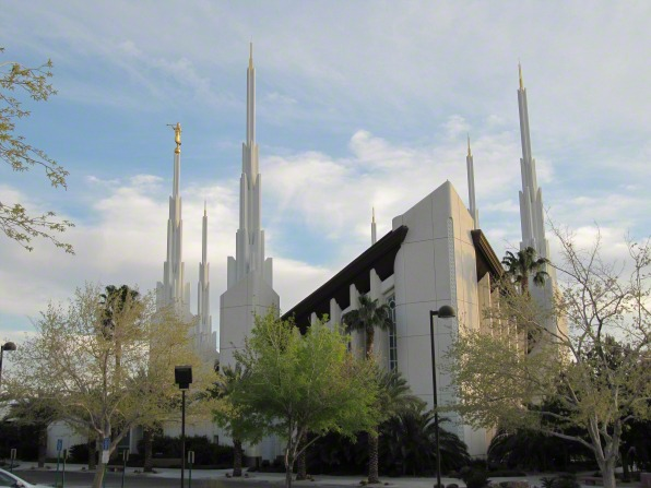 A daytime view of the front of the Las Vegas Nevada Temple, with several trees growing near the walls of the temple.