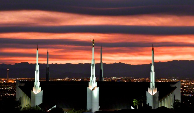 A view of the Las Vegas Nevada Temple illuminated in the evening, with an orange sky in the background and the city lights in the distance.