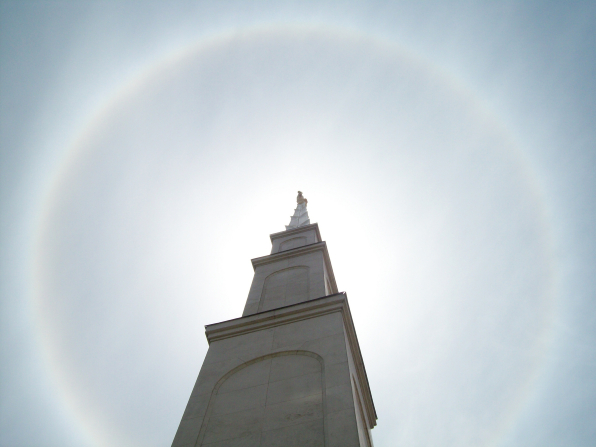 The main spire on the Lima Peru Temple seen from below, with the angel Moroni and the bright sky beyond.