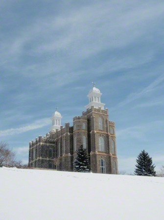 A view of the Logan Utah Temple from the bottom of the hill on a snowy day, with thin white clouds in a blue sky overhead.