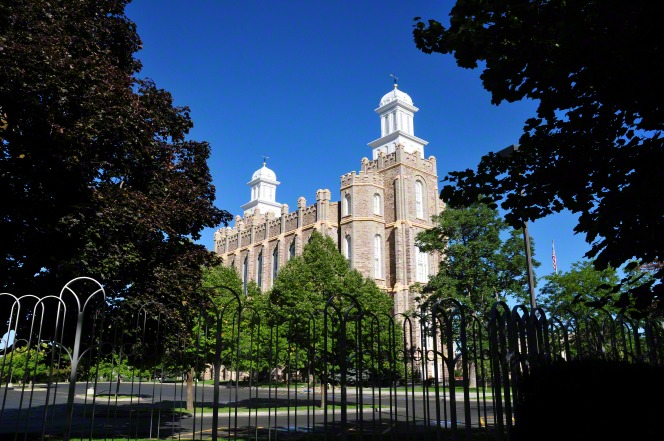 The trees on the grounds of the Logan Utah Temple framing a view of the temple, with a deep blue sky in the background and a black gate in the foreground.
