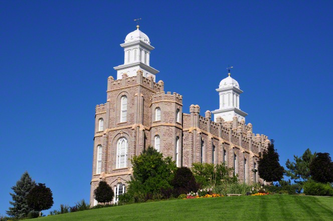 A front side view of the Logan Utah Temple in the daytime, with a clear blue sky in the background.