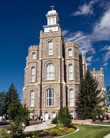 The front of the Logan Utah Temple on a sunny day, with parts of the grounds and pine trees in the foreground.