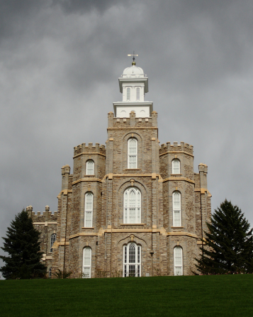The front of the Logan Utah Temple from the bottom of the hill on a stormy day, with two pine trees on either side of the temple.