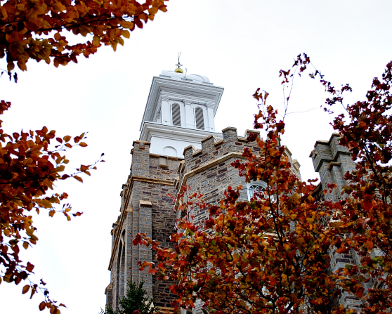 The front spire of the Logan Utah Temple on a fall day, seen between the branches of orange leaves on nearby trees.