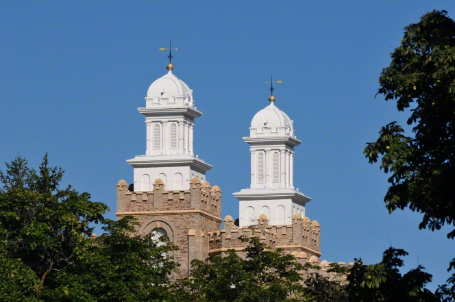 The two spires on the Logan Utah Temple, seen above the tops of green trees on a clear day.