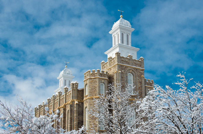The Logan Utah Temple on a sunny winter day, seen rising above snow covered trees on the temple grounds, with a blue sky in the background.