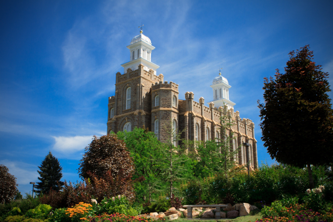 The Logan Utah Temple and grounds on a sunny day, with a large red tree on the right side and a blue sky overhead.