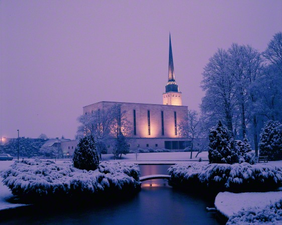 A side view of the London England Temple covered in snow on a winter evening, with the temple pond in the foreground.