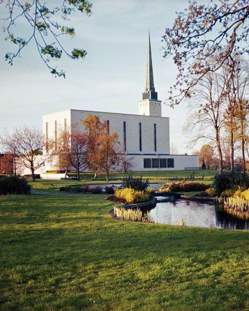 A side view of the London England Temple on a fall day, with the temple grounds and pond in the foreground.