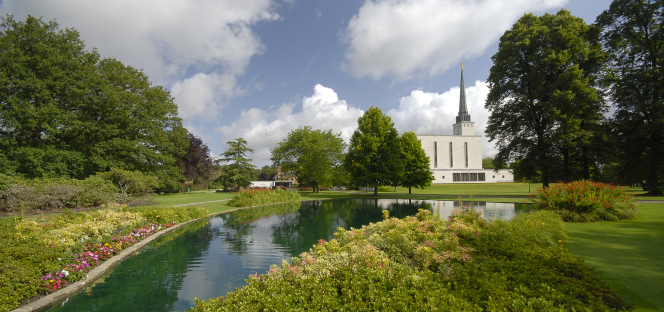 The London England Temple grounds and pond on a sunny day, with the temple seen over to the right in the distance.