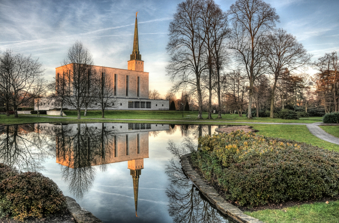 The London England Temple and bare trees on the temple ground, along with their reflection in the temple's pond on a winter day.