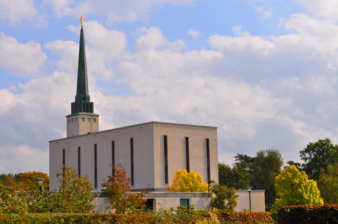 The back of the London England Temple on a fall day, showing the angel Moroni extended toward a partly cloudy sky overhead.