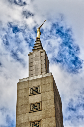 The spire on the Los Angeles California Temple, with the angel Moroni statue against white clouds in a deep blue sky.