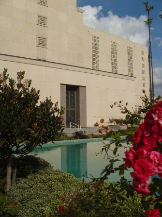A pool of water on the grounds of the Los Angeles California Temple, with pink flowers in the foreground and a door to the temple in the background.