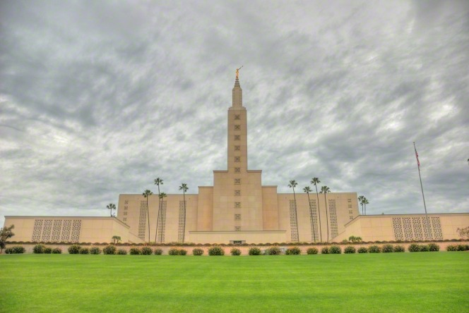The front of the Los Angeles California Temple on a stormy day, with a green lawn in the foreground.