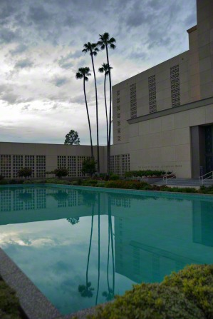 A pool of water near the Los Angeles California Temple, with three tall palm trees near the temple being reflected in the water.
