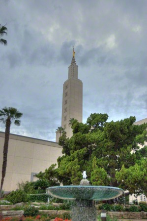 A water fountain on the grounds of the Los Angeles California Temple, with a green tree and the temple's spire in the distance.