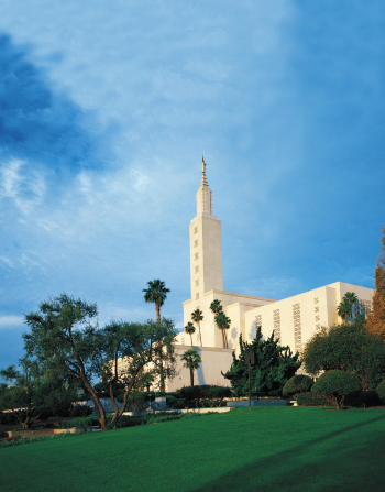 The Los Angeles California Temple seen from a distance on a sunny day, with different varieties of trees growing across the grounds.