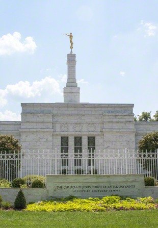 The Louisville Kentucky Temple on a sunny day, with the temple's granite name sign outside of the temple's white gate.
