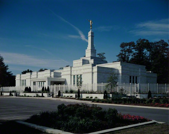 A view of the Louisville Kentucky Temple from the temple's parking lot, with a partly cloudy sky overhead.
