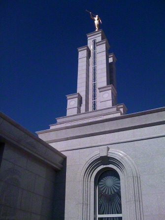 The spire and angel Moroni on the Lubbock Texas Temple, set against a deep blue sky.