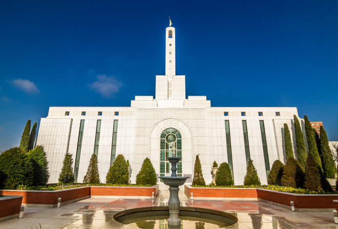 A side view of the Madrid Spain Temple, with a water fountain feature and stained-glass windows, on a sunny day with a blue sky behind.