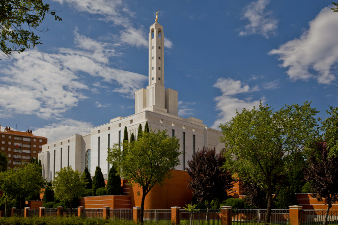 The Madrid Spain Temple exterior in the daytime, surrounded with trees, with a cloudy sky beyond.
