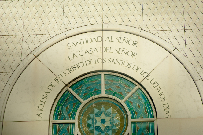 "A close-up of a stained-glass window and an inscription that reads, ""Holiness to the Lord: The House of the Lord"" in Spanish on the exterior of the Madrid Spain Temple."