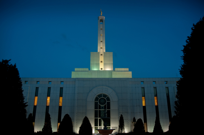 The exterior of the Madrid Spain Temple lit up with glowing lights at twilight.